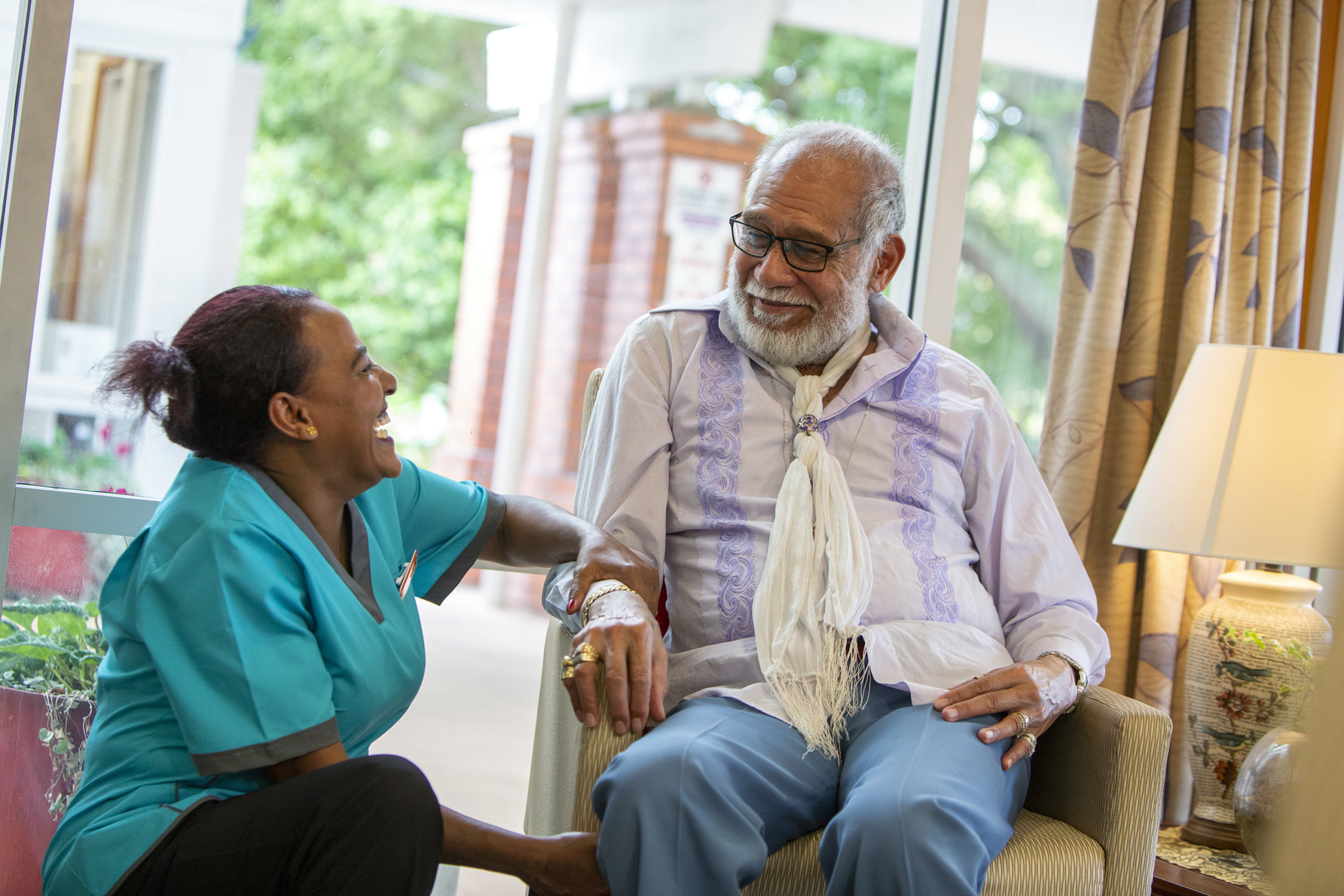 Care resident laughing with Healthcare Assistant