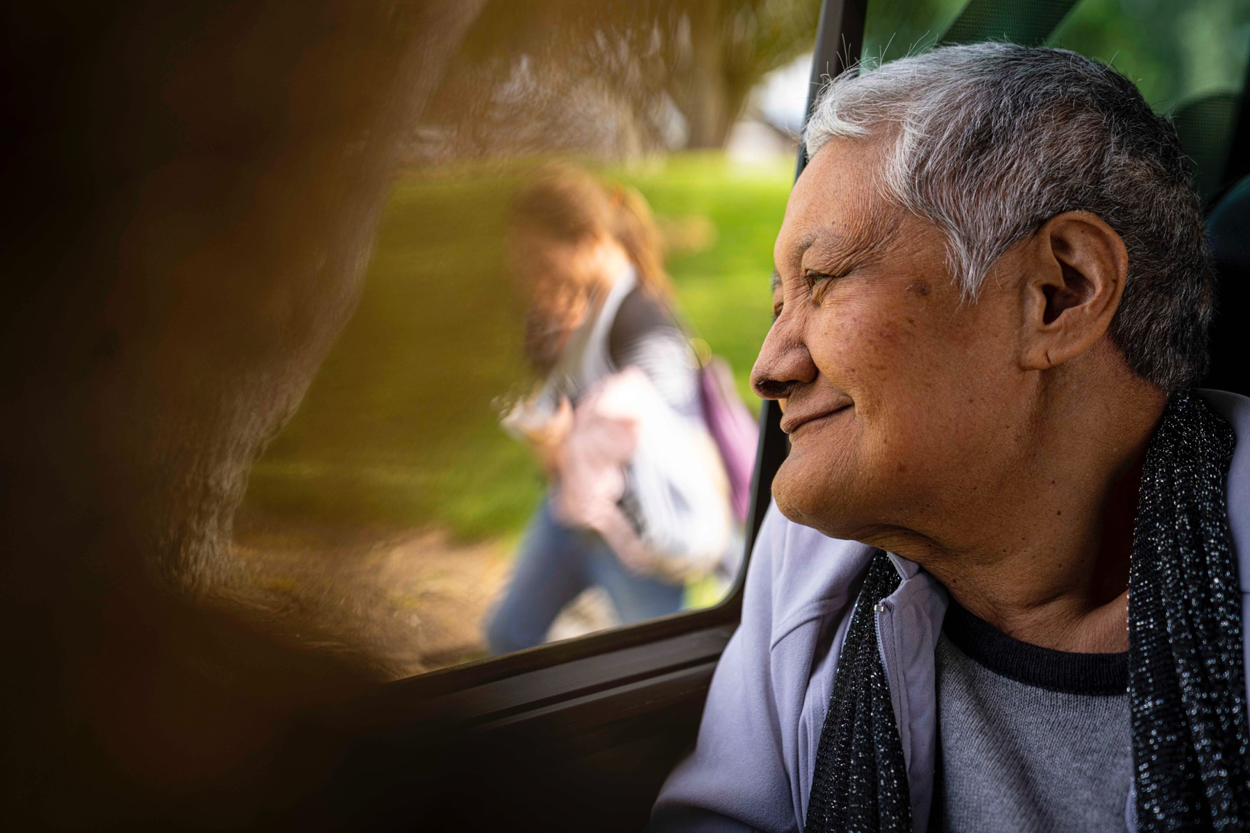 Oceania resident smiling outside a car window on a van trip