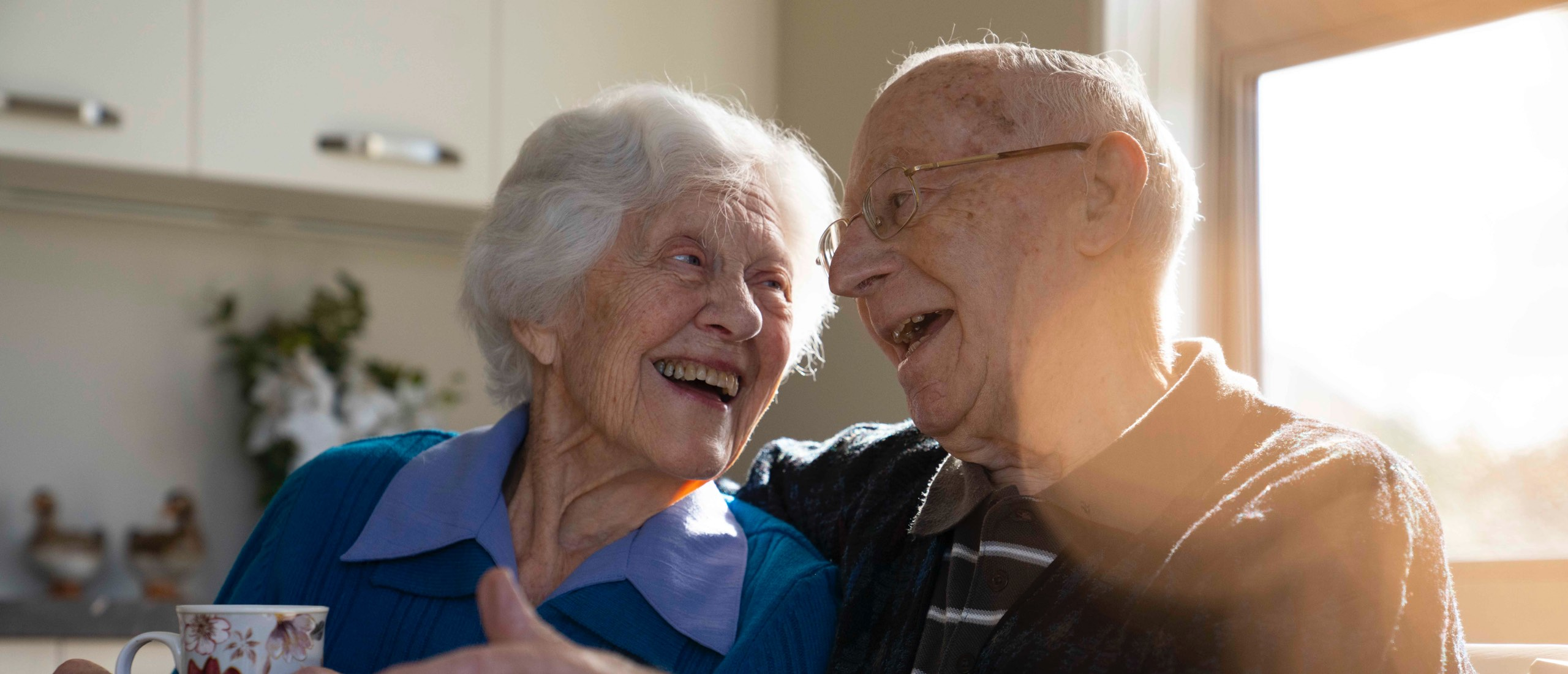 Oceania couple laughing in their Care Suite
