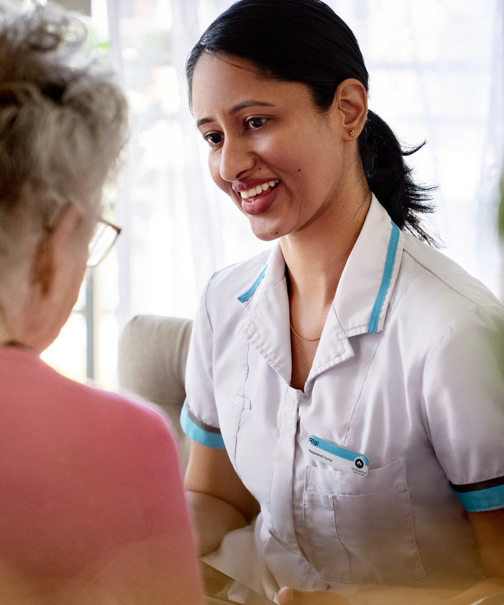 Oceania nurse smiling with a resident