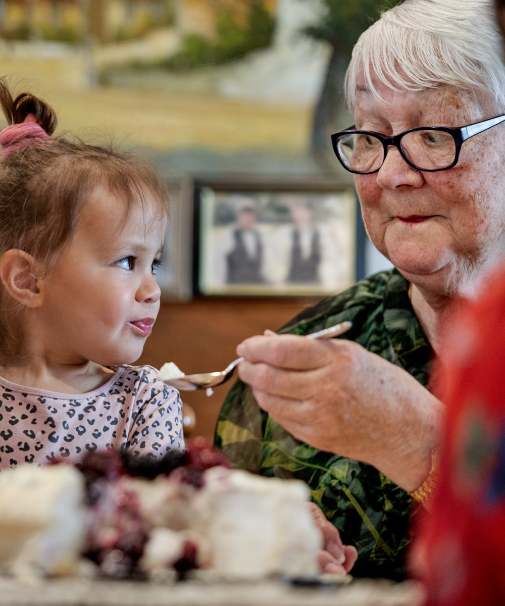 Oceania resident sharing dessert with young girl